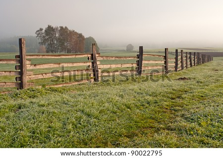 View of a wooden fence on a field. - stock photo