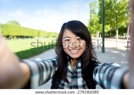 View of a Young attractive asian tourist in Paris taking selfie - stock photo