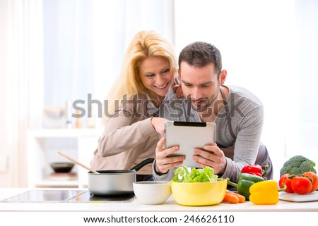 View of a Young attractive couple reading recipe on a  tablet - stock photo