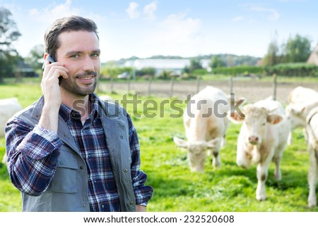 View of a Young attractive farmer using mobile phone in a field - stock photo