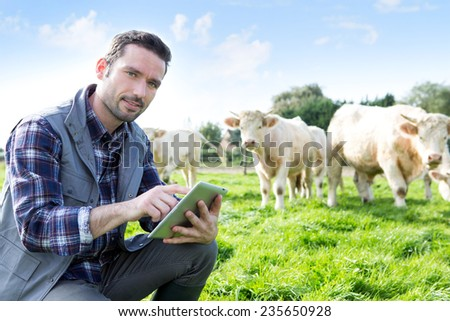 View of a Young attractive farmer using tablet in a field - stock photo