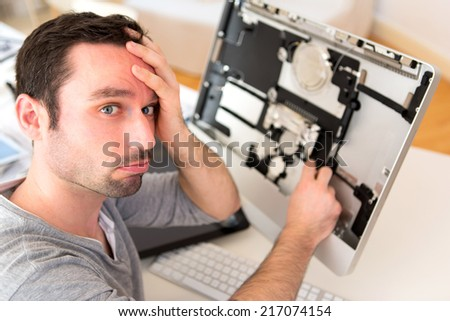 View of a Young attractive man trying to repair computer