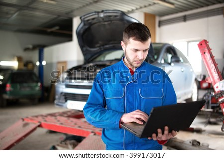 View of a Young attractive mechanic working at the garage