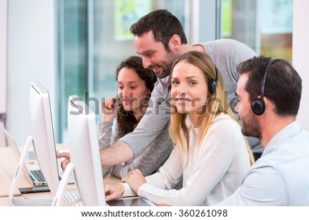View of a Young attractive people learning their new job at call center