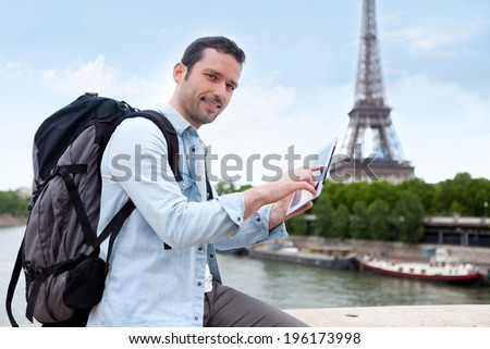 View of a Young attractive tourist using tablet in Paris, France - stock photo