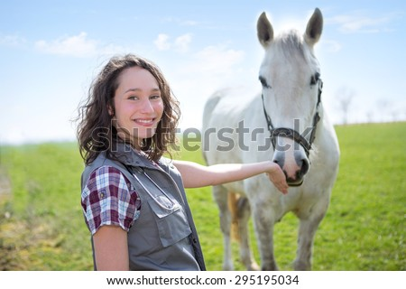 View of a young attractive veterinary in fields with horse - stock photo