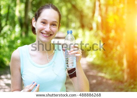 View of a Young attractive woman drinking water after a running session