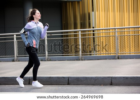 View of a Young attractive woman running downtown - stock photo