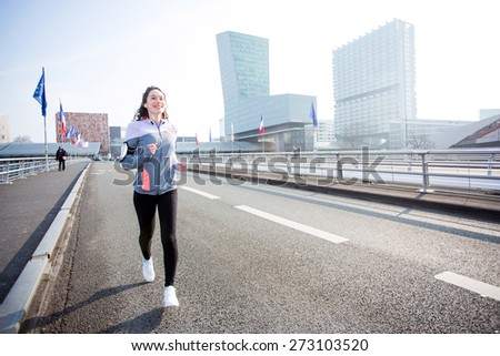 View of a Young attractive woman running downtown