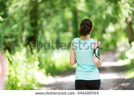View of a Young attractive woman running in the forest - stock photo
