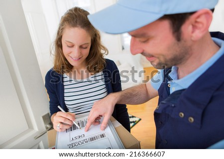 View of a Young attractive woman signing on delivery paper