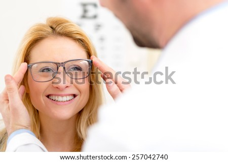 View of a Young attractive woman trying glasses w optician - stock photo