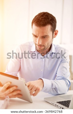 View of a Young business man working at home on his laptop - stock photo