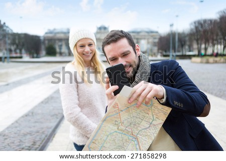 View of a Young couple on holidays taking pictures in the city - stock photo