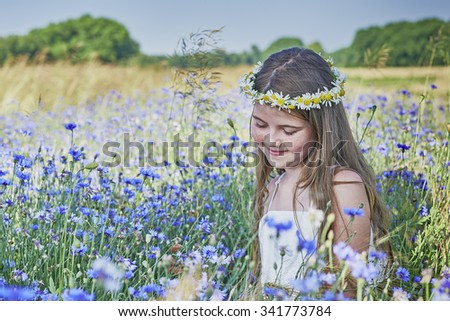 View of a young girl sitting in cornflower - stock photo