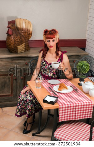 View of a young woman inside a coffee shop having breakfast.