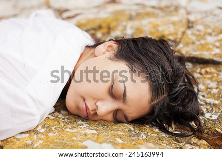 View of a young woman washed up on rocks at the edge of a river, possible boating accident victim - stock photo
