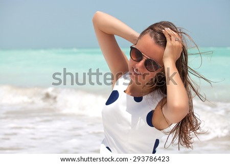 View of a young woman with the wind in her hair. Fashion shot on the beach. Beauty in the summer sun.