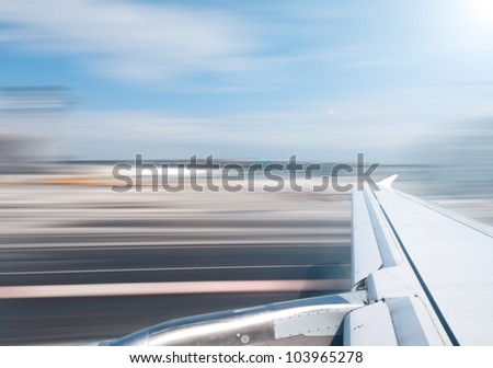 View of air plane wing during take off or landing. Motion blur of airport grounds and sky. - stock photo