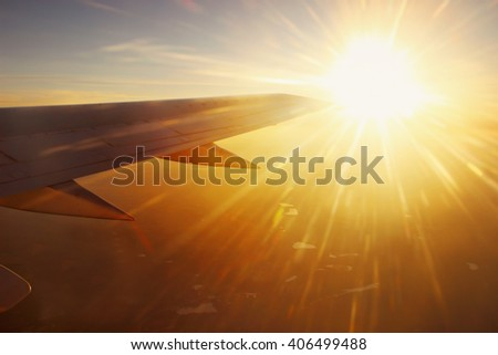 View of airplane wing and sun beams though the window. - stock photo