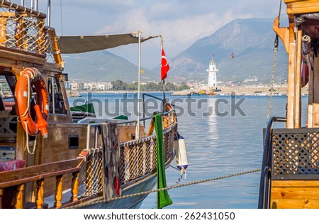 View of Alanya bay, lighthouse and mountains with tourists ships on the foreground - stock photo