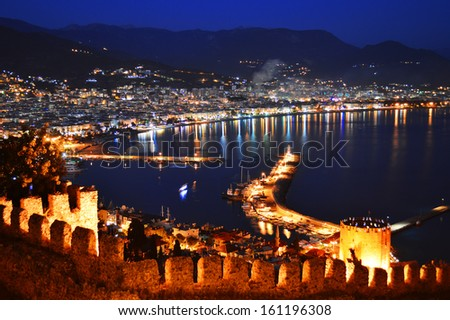 View of Alanya harbor from Alanya peninsula. Turkish Riviera by night - stock photo