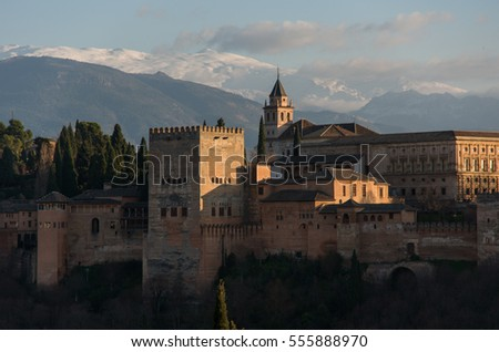 View of Alhambra Palace in Granada, Spain with Sierra Nevada mountains in snow at the background . Granada, Spain.