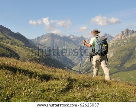 View of Alps mountains and a tourist standing on a footpath.