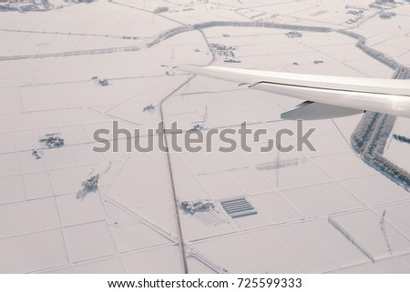 View of an airplane wing with snows on land