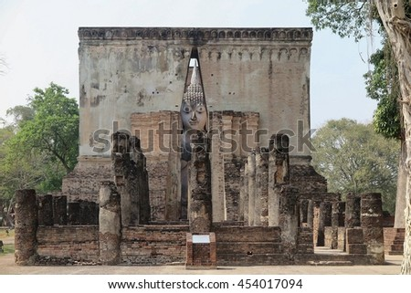 View of an ancient Buddha statue behind the gate to Temple Wat Si Chum in Sukhothai Historical Park, Thailand ~ A giant sitting Buddha image with the posture of Subduing Mara inside a buddhist shrine - stock photo