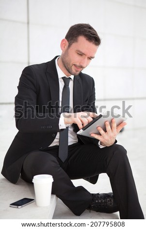 View of an attractive businessman using a tablet - stock photo