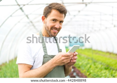 View of an attractive farmer in a greenhouse using mobile
