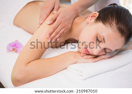 View of an attractive young woman receiving shoulder massage at spa center - stock photo