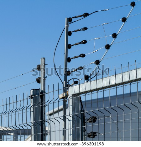 view of an electric fence installation on a metallic grilled fence - stock photo