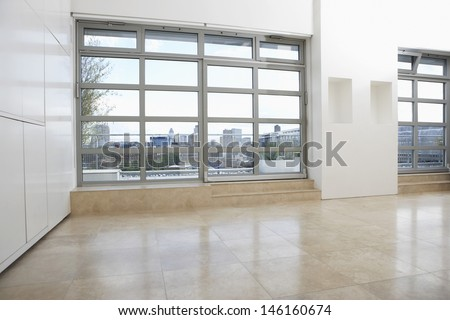 View of an empty apartment with tiled flooring and windows - stock photo