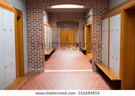 View of an empty brick walled corridor with tiled flooring in college - stock photo