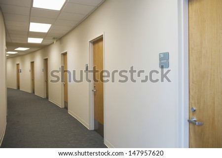View of an empty corridor with closed doors - stock photo