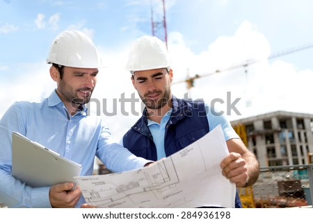 View of an Engineer and worker checking plan on construction site  - stock photo