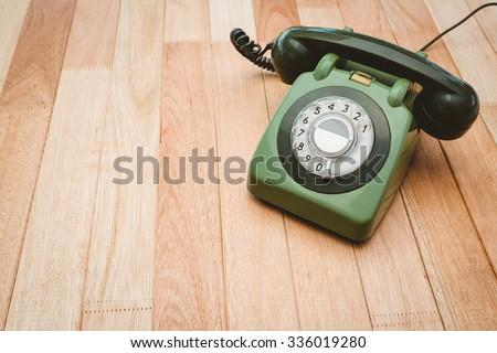 View of an old phone on wood desk - stock photo