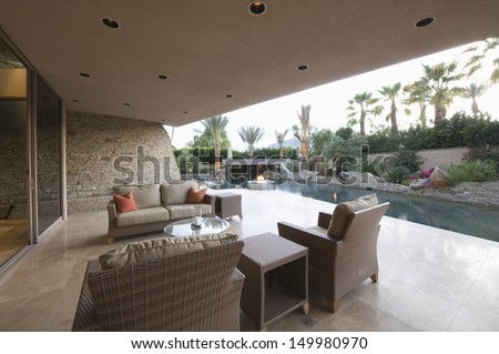 View of an outdoor room by swimming pool of a modern home - stock photo