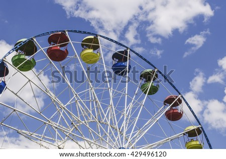 View of an upper part of a Ferris wheel against bright blue sky  - stock photo