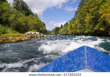 View of approaching white water on a bright summer day from a drift boat on Oregon's Mckenzie River near Eugene Oregon. - stock photo