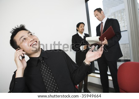 View of architect talking on mobile phone with businesswoman and manager discussing in background. - stock photo