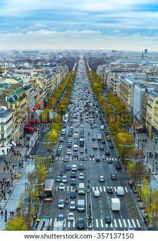 View of avenue des Champs Elysees in Paris from the Arc de Triomphe. Autumn. Rain. Sun. - stock photo