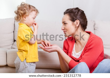 View of baby eating snacks with mother - stock photo