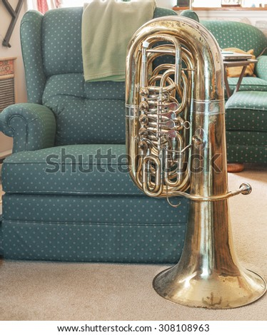 View of bass tuba in a comfortable, home setting, next to an easy chair/recliner.