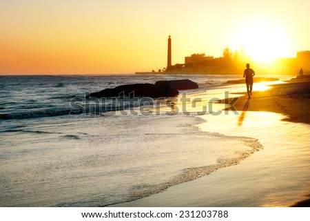 View of beach and lighthouse Maspalomas at sunset.  Gran Canaria. - stock photo