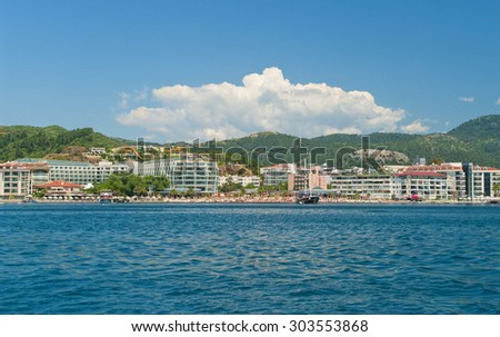 view of beach with hotels, umrellas and sunbeds from sea against blue sky with cloud and water slides at background, Marmaris, Turkey - stock photo