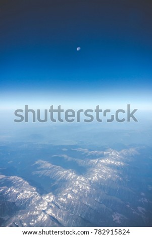 View of beautiful caucasus mountains from an airplane with moon in the background and clear skies