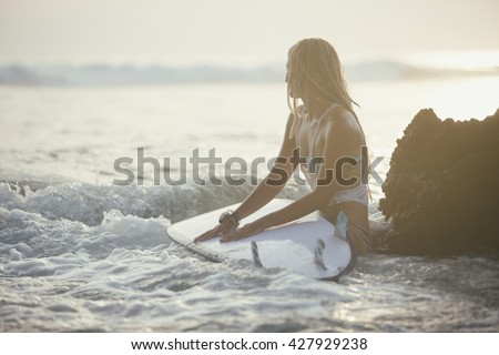 View of beautiful sexy young woman surfer girl in bikini with white surfboard on a beach at sunset or sunrise - stock photo